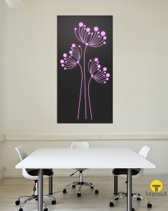 Black laser cut panel with purple flowers pattern, standing on grey wall behind white office table with three white chairs