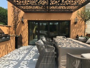 Laser cut rooftop pergola with olive tree pattern casting shadow on the big garden table