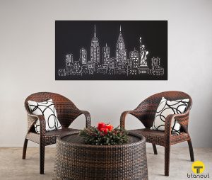 Black laser cut metal panel with New York cityscape pattern, on a grey wall, behind two chairs and a round table
